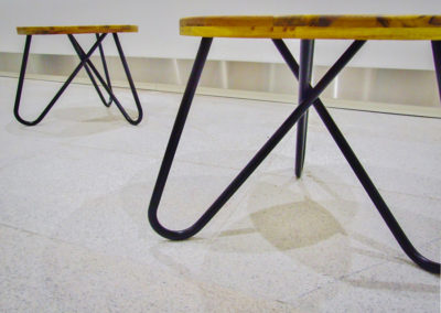 kovové podnoží a desky dvou kulatých stolků v detailu