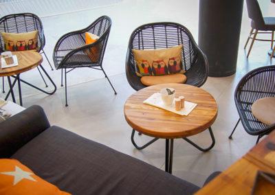 Kulatý do žluta laděný stolek JUA v kavárenském prostředí, obklopen židlemi